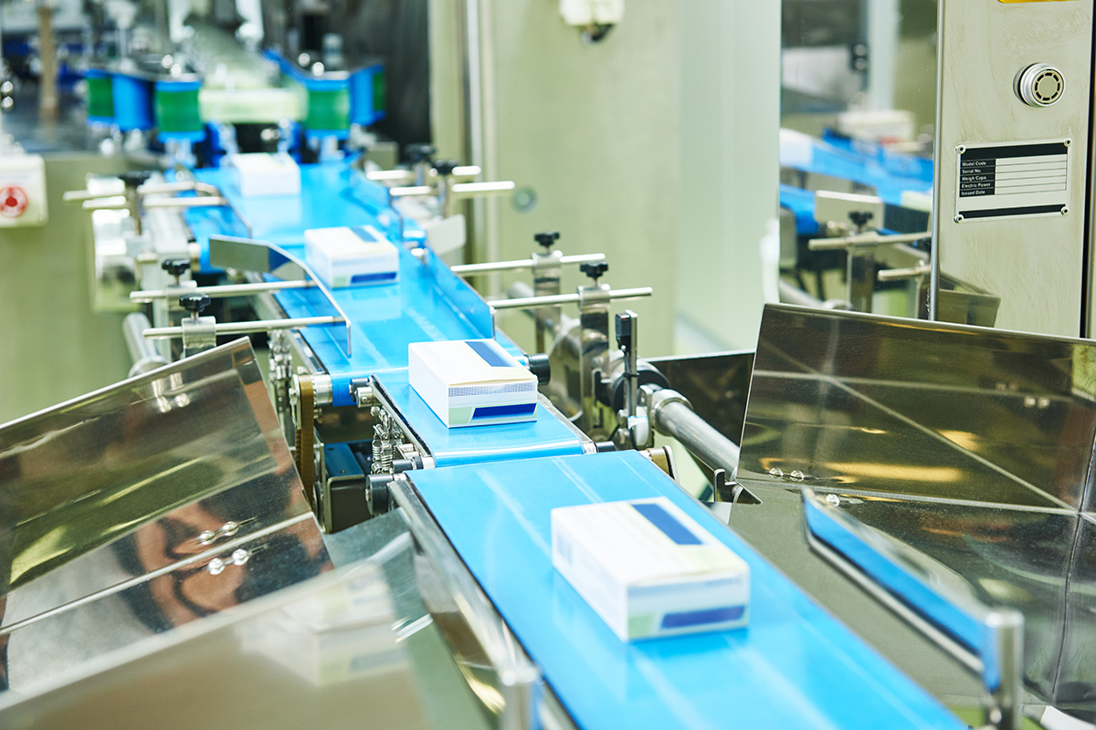 pharmaceutical packing production line conveyer at manufacture pharmacy factory. Authentic shot in challenging conditions. maybe little blurred