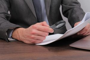 Close up of businessman using loupe for reading contract. Magnifying Glass and document. Lawyer minutely checking documents